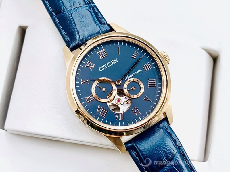 Mặt đồng hồ và dây da màu xanh sang trọng, điểm nhấn với nền mặt số chân kính được thiết kế độc đáo phô diễn ra bộ máy cơ đầy nam tính.